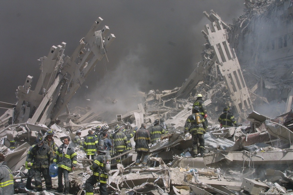 Firefighters walk through the rubble in the aftermath of the September 11 attacks.(AP Photo/Shawn Baldwin)