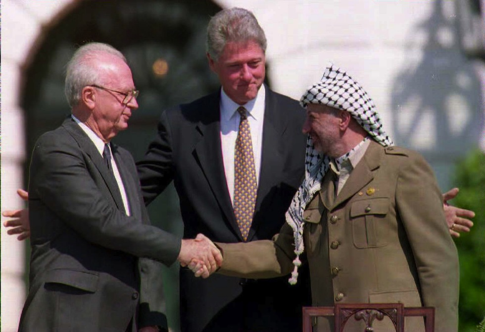 This 13 September 1993 file photo shows US President Bill Clinton (C) standing between PLO leader Yasser Arafat (R) as he shakes hands with Israeli Prime Minister Yitzahk Rabin. Rabin and Arafat shook hands for the first time after Israel and the PLO signed a historic agreement on Palestinian autonomy in the occupied territories. Rabin was assassinated reportedly by a Jewish extremist 04 November after attending a peace rally in Tel Aviv. AFP PHOTO/J. David AKE (Photo credit should read FILES/J. David AKE/AFP/Getty Images)