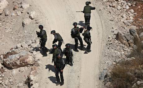 epa03918911 Israeli soldiers move in during clashes with Palestinians from the West Bank village of Bil'in in a military operation that led to the death of Palestinian Islamic Jiahd militant Mohamed Aatzi in the village near Ramallah, West Bank, 22 October 2013. Aatzi reportedly was killed during an exchange of fire with Israeli forces after attempting to arrest him in a cave where he was hiding next to the West Bank village of Bil'in, 22 October 2013. Aatzi was wanted for allegedly helped to plan a bomb attack on a Tel Aviv bus on 21 November 2012, in which 29 passengers were wounded.  EPA/ATEF SAFADI