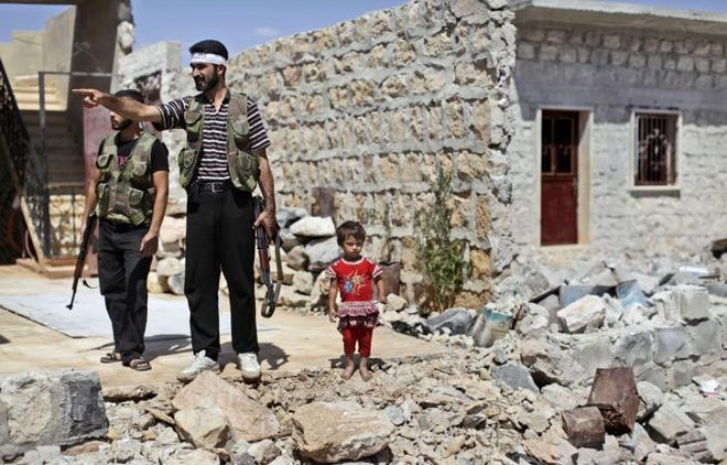 A Syrian child stands next to rebel fighters checking a house that was damaged in bombing by government forces in Marea, on the outskirts of Aleppo, Syria, Tuesday, Sept. 4, 2012. (AP Photo/Muhammed Muheisen)
