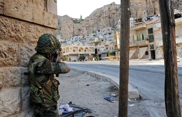 In this Wednesday, Sept. 11, 2013 photo released by the Syrian official news agency SANA, a Syrian government solider aims his weapon during clashes with Free Syrian Army fighters, not pictured, in Maaloula village, northeast of the capital Damascus, Syria. Heavy fighting between Syrian government troops and rebels flared again on Wednesday, Sept. 11, 2013 in the ancient, predominantly Christian village of Maaloula. Troops are trying to flush out rebel units, including two that are linked to al-Qaida, from the hilltop enclave which they broke into last week. (AP Photo/SANA)