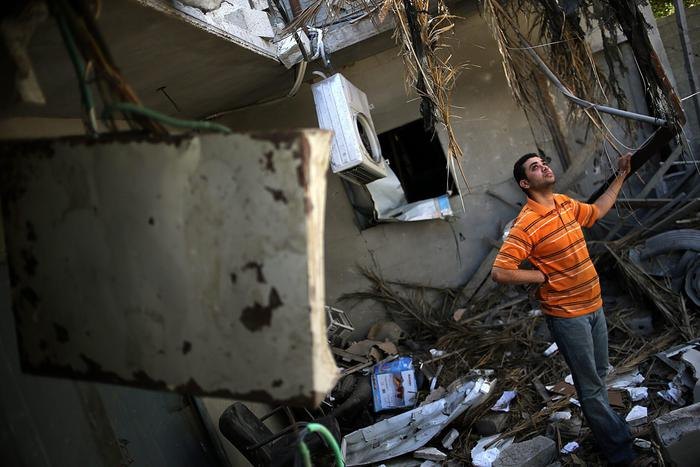 epa04260650 A Palestinian inspects the rubble of his destroyed house after Israeli air strikes in the southeast of Gaza City, early 16 June 2014. Israeli military said it carried out air strikes on five weapons and militant sites in Gaza, following overnight rocket fire from te coastal strip into Israel.  EPA/MOHAMMED SABER