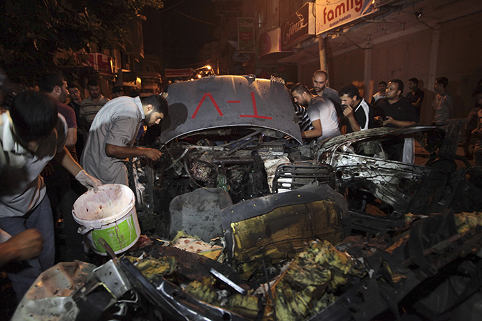 "Palestinians inspect the remains of a car which police said was hit in an Israeli air strike in Gaza City July 9, 2014. An Israeli aircraft targeted a civilian car in the center of Gaza City's busiest shopping street on Wednesday night and at least one person in the car, the driver, was killed, medics said.Video of the destroyed car showed it had large red stickers that read ""TV"". The killed driver, Hamed Shehab, 30, worked for the Gaza-based news website Media 24. A Media 24 journalist told Reuters that Shehab was occasionally called in to work as a driver when news events warranted. The Israeli military had no initial comment on the strike, and a spokeswoman said she was checking for details. REUTERS/Ashraf Amrah (GAZA - Tags: POLITICS CIVIL UNREST MEDIA TPX IMAGES OF THE DAY) - RTR3XWPR"