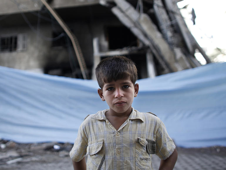 TOPSHOTS A Palestinian young boy poses in front of a tarpaulin hiding a destroyed building following an Israeli air strike on July 14, 2014 in Gaza City. Israel kept up its punishing raids on Gaza on July 14, 2014 but held off from a threatened ground incursion as the world intensified efforts to broker a truce. AFP PHOTO / THOMAS COEX