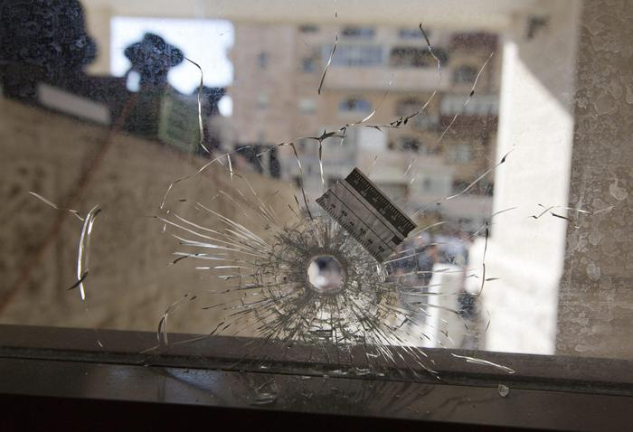 epa04494512 A bullet hole in a synagogue's front glass seen from inside and looking outwards to the Har Nof neighborhood in Jerusalem, 18 November 2014. Media reports state that two Palestinians armed with an axe, kitchen knives and a pistol killed four worshippers and injured eight others at a Jerusalem synagogue early 18 November, before being shot dead by Israeli police. The attack, which lasted seven minutes until the first police arrived, occurred during morning prayers.  EPA/JIM HOLLANDER