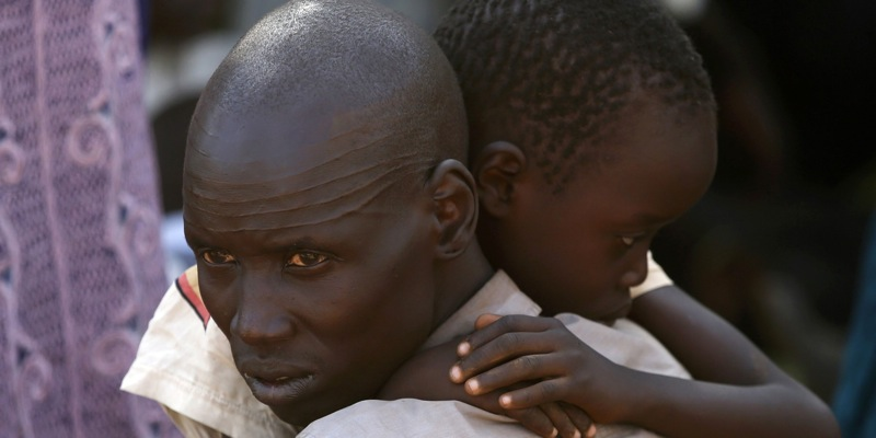 An internally displaced man holds his son inside a United Nations Missions in Sudan (UNMIS) compound in Juba December 19, 2013. South Sudanese government troops battled to regain control of a flashpoint town and sent forces to quell fighting in a vital oil producing area on Thursday, the fifth day of a conflict that that has deepended ethnic divisions in the two-year-old nation. REUTERS/Goran Tomasevic (SOUTH SUDAN - Tags: POLITICS CIVIL UNREST)