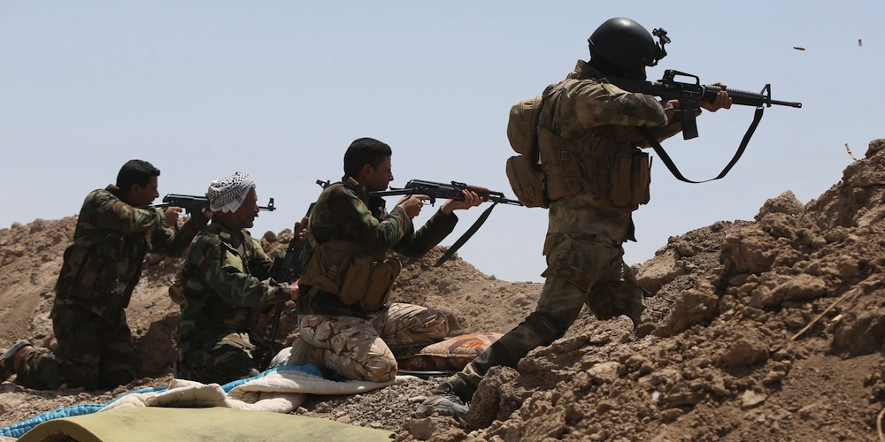 Iraqi soldiers and Shiite fighters from the popular committees hold a post as they fire towards Islamic State (IS) group positions in the Garma district of Anbar province west of the Iraqi capital Baghdad, on May 19, 2015.  Iraq's army and allied paramilitary forces massed around Anbar's provincial capital Ramadi, looking for swift action to recapture the city from the Islamic State group before it builds up defences. AFP PHOTO / AHMAD AL-RUBAYE         (Photo credit should read AHMAD AL-RUBAYE/AFP/Getty Images)