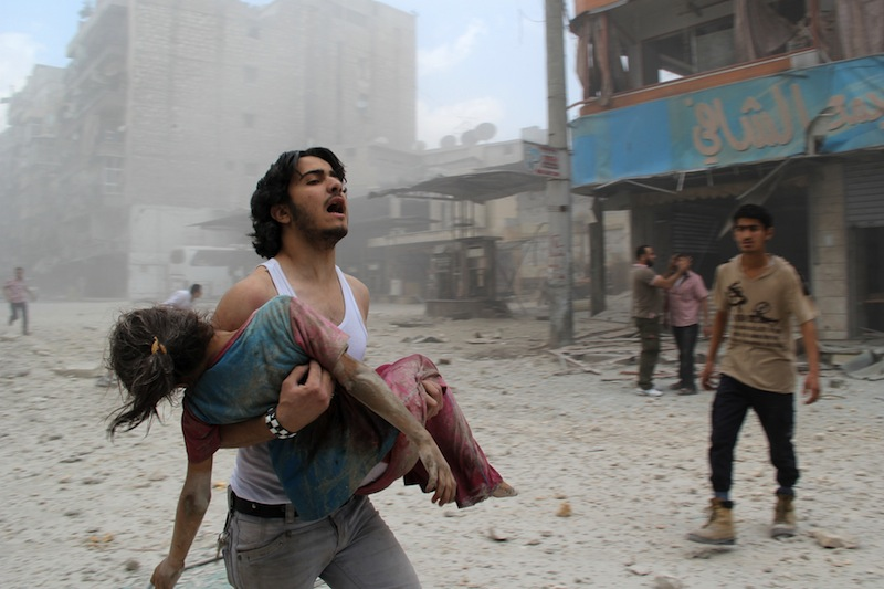 A man carries a young girl who was injured in a reported barrel-bomb attack by government forces on June 3, 2014 in Kallaseh district in the northern city of Aleppo. Some 2,000 civilians, including more than 500 children, have been killed in regime air strikes on rebel-held areas of Aleppo since January, many of them in barrel bomb attacks. AFP PHOTO / BARAA AL-HALABI        (Photo credit should read BARAA AL-HALABI/AFP/Getty Images)