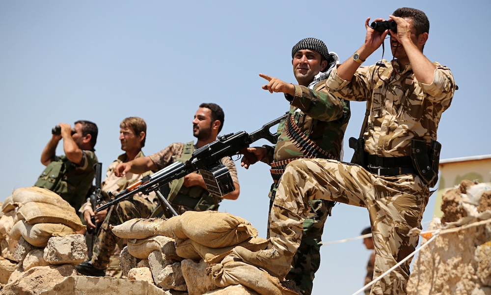 Kurdish peshmerga fighters take position in Bashiqa, near Mosul.