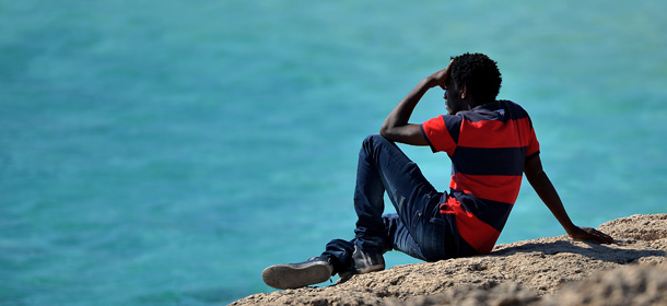 A migrant sits on rocks and stares at the sea in Lampedusa island on October 26, 2013. There are currently three navy vessels on patrol, along with six coast guard patrol boats and six border guard patrol boats, as well as helicopters and planes from each of the three agencies patrolling the area as part of the new 'Mare Nostrum' surveillance and rescue operation, launched after more than 400 migrants drowned in two disasters earlier this month. Nearly 800 refugees were rescued off Sicily in several operations as European leaders grapple with the issue of illegal immigration at a European Union summit.   AFP PHOTO /Filippo MONTEFORTE        (Photo credit should read FILIPPO MONTEFORTE/AFP/Getty Images)