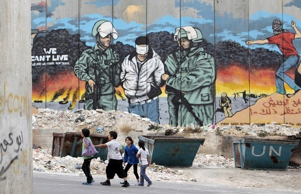 Children walk in front of a mural painted on part of Israel's controversial barrier at Aida refugee camp in the West Bank town of Bethlehem, ahead of Nakba May 14, 2012. On May 15 Palestinians will mark Nakba, or catastrophe, of Israel's founding in a 1948 war, when hundreds of thousands of their brethren fled or were forced to leave their homes. REUTERS/Ammar Awad (WEST BANK - Tags: POLITICS CIVIL UNREST)