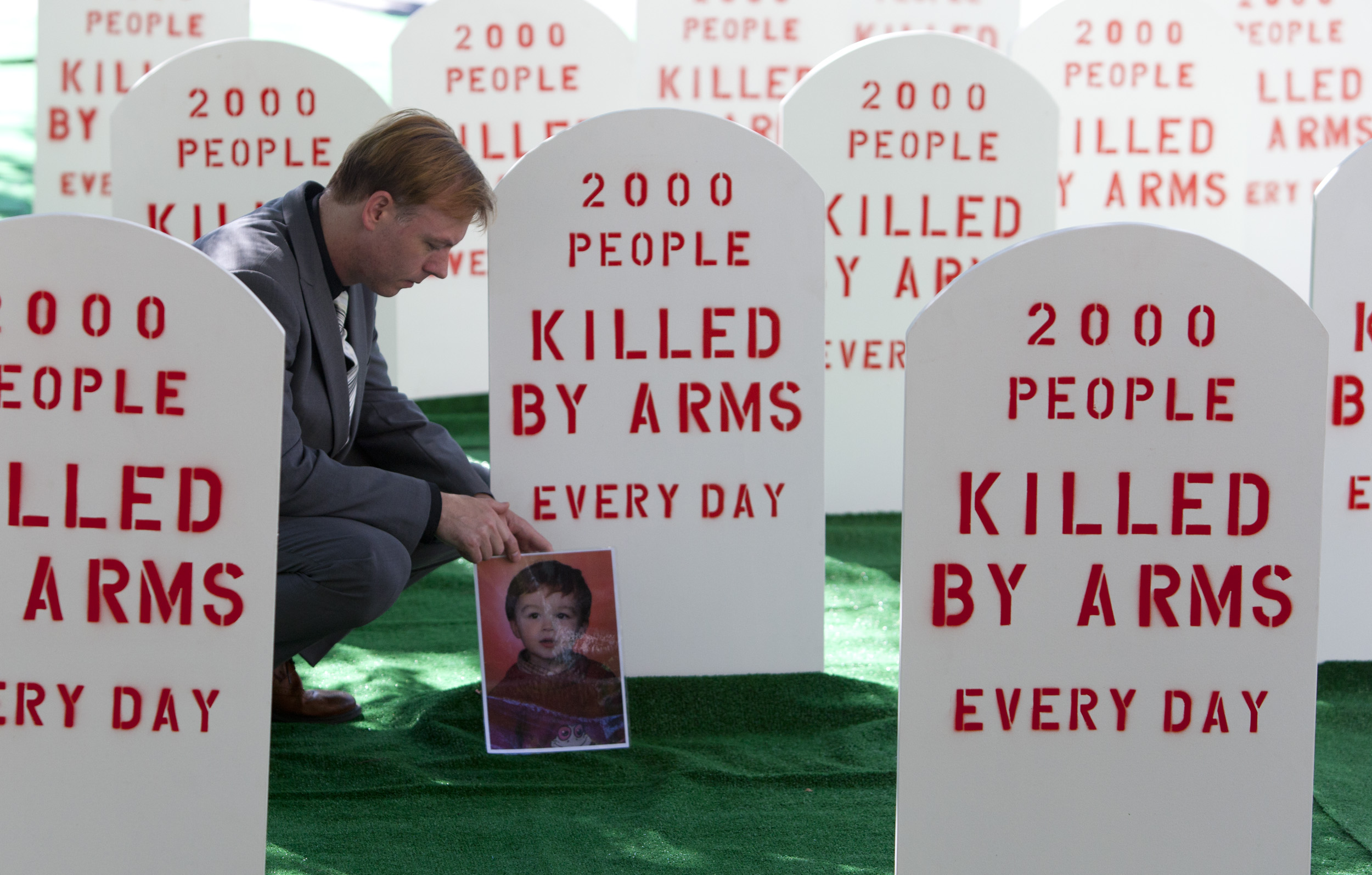Control Arms campaigner David Grimason lays a photo of his son Alistair, who was killed by stray bullets in a gun fight, at the base of a mock tombstone. Control Arms coalition set up a mock graveyard next to the United Nations building in New York July 25, 2012. They are demonstrating as the negotiations for an Arms Trade Treaty comes to a close on Friday.  Control Arms/ Andrew Kelly