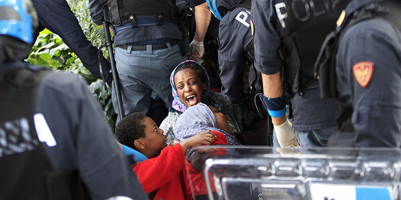 "Italian police officers surround a family of migrants during an operation to remove them from the Italian-French border in the Italian city of Ventimiglia on June, 16, 2015.  Italy and France engaged in a war of words as a standoff over hundreds of Africans offered a graphic illustration of Europe's migration crisis. Italian Interior Minister Angelino Alfano described images of migrants perched on rocks at the border town of Ventimiglia after being refused entry to France as a ""punch in the face for Europe.""  AFP PHOTO / JEAN CHRISTOPHE MAGNENET        (Photo credit should read JEAN CHRISTOPHE MAGNENET/AFP/Getty Images)"