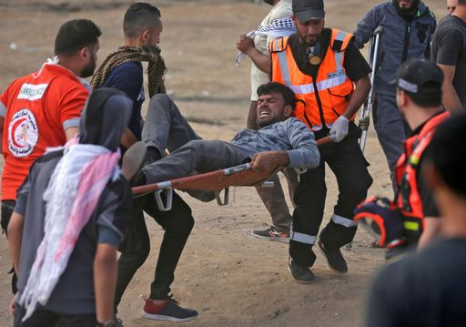 Palestinians carry a demonstrator injured during clashes with Israeli forces near the border between the Gaza strip and Israel east of Gaza City on May 14, 2018, during a demonstration on the day of the US embassy move to Jerusalem. The US moves its embassy in Israel to Jerusalem later Monday after months of global outcry, Palestinian anger and exuberant praise from Israelis over President Donald Trump's decision tossing aside decades of precedent. There are concerns that the Gaza protests less than 100 kilometres (60 miles) away will turn deadly if Palestinians attempt to damage or cross the fence with Israeli snipers positioned on the other side. / AFP PHOTO / MAHMUD HAMS
