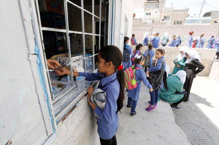 A refugee schoolchild buys sweets on her first day of the new school year at one of the UNRWA schools at a Palestinian refugee camp al Wehdat, in Amman, Jordan, September 1, 2016.  REUTERS/Muhammad Hamed