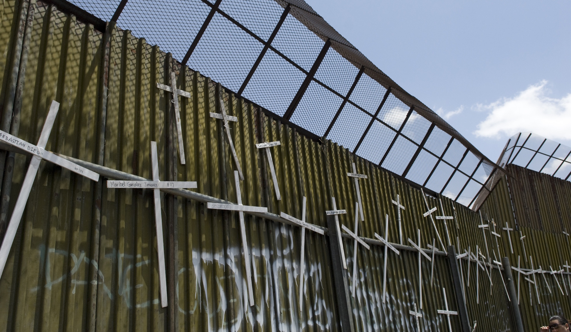 Crosses hang on the Mexican side of the border wall in Nogales, Mexico, commemorating the 4,000 people who have lost their lives attempting to cross the desert in search of a better life in the United States.