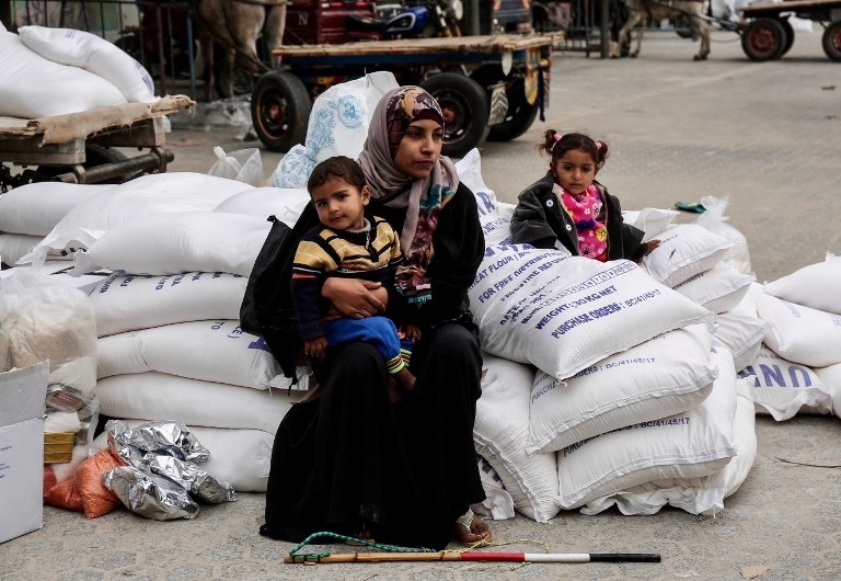 """A Palestinian woman sits with a child after receiving food supplies from the United Nations' offices at the United Nations' offices in the Khan Yunis refugee camp in the southern Gaza Strip on February 11, 2018. On January 16, Washington held back $65 million that had been earmarked for the UN Relief and Works Agency for Palestinian refugees (UNRWA), but the State Department denied the freeze was to punish the Palestinian leadership, which has cut ties with President Donald Trump's administration following his recognition of Jerusalem as Israel's capital last year, with a spokeswoman saying it was linked to necessary """"reform"""" of UNRWA. / AFP PHOTO / SAID KHATIB"""